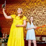 """Das knallige Gelb des Spitzenkleides schmeichelt der blonden Mähne von Prinzessin Amalia (li.). Für den """"Koningsdag 2020"""", dem niederländischen Nationalfeiertag, hat sich die älteste Tochter von Königin Máxima gleich für zwei Trend-Teile entschieden: ein Off-Shoulder-Dress und sommerliche Espadrilles-Wedges. Auch ihre jüngere Schwester, Prinzessin Ariane, hat einen ähnlichen Look in Hellblau gewählt."""