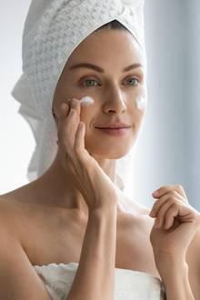 Fettige Haut: Frau trägt Gesichtscreme auf.