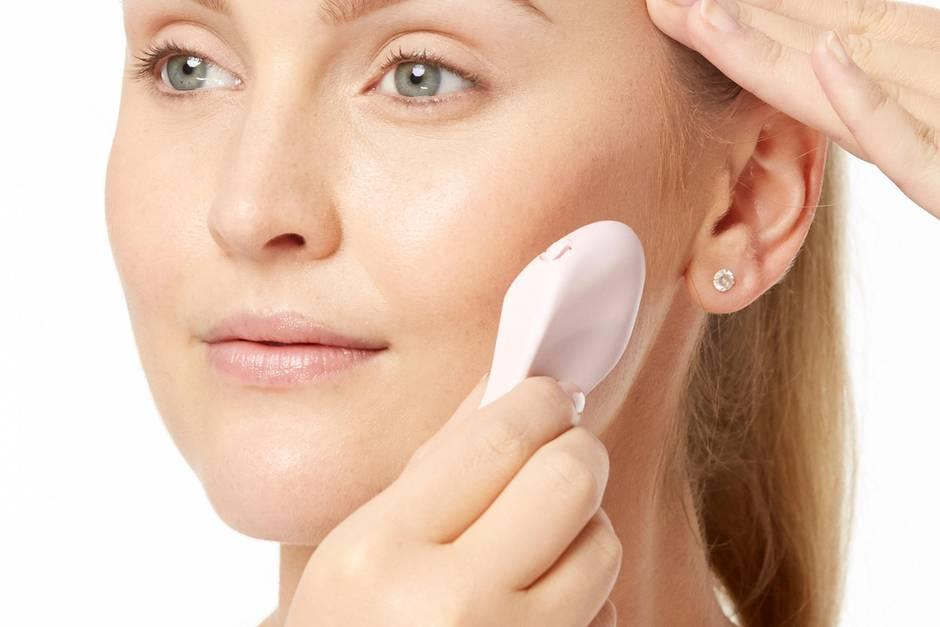 Frau wendet Dermaplaner zur Entfernung von Gesichtsbehaarung an