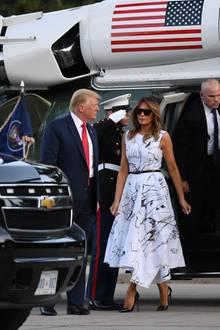 """The show must go on: Auch die tiefe Krise und aktuelle Spaltung der USA infolge der Corona-Pandemie und der anhaltenden Proteste gegen Rassismus halten Donald Trump und Ehefrau Melania nicht davon ab, zum Unabhängigkeitstag am 4. Juli 'business as usual' zu machen. Bei den Vorbereitungen zu den Feierlichkeiten in South Dakota wählt Melania Trump ein Kleid mit einem Skizzen-Print von Alexander McQueen, dazu Pumps vonChristian Louboutin undeinedunkle Sonnenbrille. Das Besondere: An demKleid, das mehrere tausend Euro kostet, waren rund ein Dutzend Menschen beteiligt: Zuerstfertigten Studenten Skizzenvon """"tanzenden Mädchen""""an, die dannim Nachhinein auf das Leinenkleid von Hand bestickt wurden.Eine aufwendige Teamarbeit, die im Internet jedoch auch einige kritische Kommentare hervorbringt. So fragt sich ein User, ob nicht Ehemann Donald Trump dasKleid bemalt habe..."""