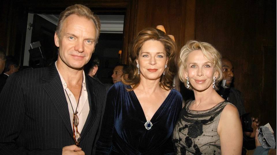 Königin Noor (Mitte) mit Sänger Sting und SchauspielerinTrudie Styler bei einem Dinner in New York im November 2005. Im tiefen Ausschnitt ihres samtblauen Kleides steckt die Brosche mit dem blauen Saphir.