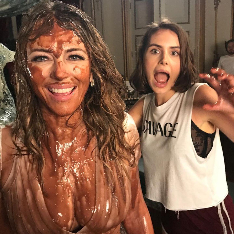 """Oh je, was ist denn mit Liz Hurley passiert? Bei Dreharbeiten zu der Serie """"The Royals"""" muss sie eine Szene spielen,in der sie in einen Schokoladenbrunnen fällt. Auf Instagram beschreibt Liz Hurley die lustige Szene so: """"Keiner meiner Lieblingstage während der Dreharbeiten zu The Royals. Ich sollte in einen Schokoladenbrunnen fallen - natürlich war es keine Schokolade und es gab viele Einstellungen. Die Crew hat es aber genossen."""""""