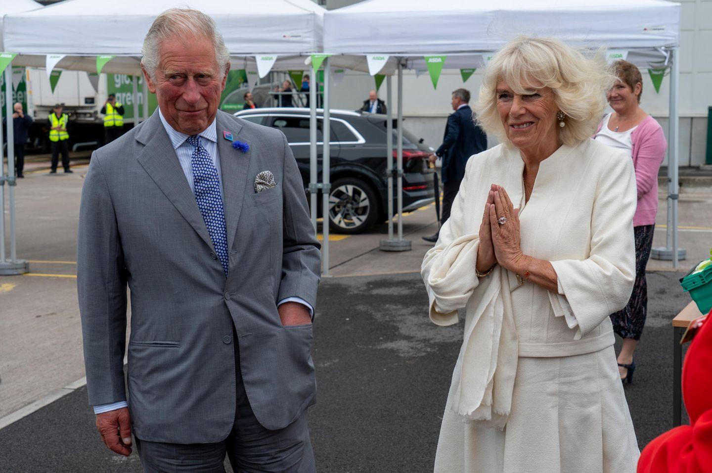 """9. Juli 2020  Prinz Charles und Herzogin Camilla besuchen ein Distributionszentrumder Supermarktkette ASDA in Bristol. Wegen des Coronavirus' ist Händeschütteln tabu ist. Kein Problemfür die Herzogin: Sie grüßt mit zusammengefalteten Händen, der sogenannten""""Namasté""""- Geste."""