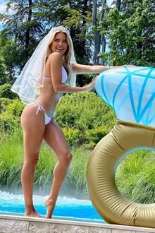 """Was für ein Look! Sylvie Meis posiert in einem weißen Bikini mit Schleier im Haar und einem XXL-Aufblasbaren-Verlobungsring am Pool eines Luxus-Resorts. Was es zu feiern gibt? Natürlich ihren Junggesellinnen-Abschied. Denn lange dauert es nicht mehr, bis sie ihrem Niclas Castello das """"Ja""""-Wort geben wird.."""