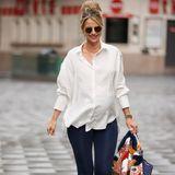 Vogue Williams macht vor, wie man einen Casual Look aus Hemdbluse und Jeans aufpeppt. Einfach dazu knallige Accessoires wie fransige High Heels in Rot und eine auffällige Statementjacke - die hier über eine Tasche gelegt wurde - kombinieren. Fertig ist die britische TV- und Radio-Moderatorin für Londons Straßen.