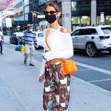 """Eine Hose mit 70er-Jahre-Playboy-Cover-Print? Model Bella Hadid kanns tragen und weiß die ungewöhnliche Hose sogar in Szene zu setzen. Sie greift die Farben einfach in ihrem Outfit auf. Ein weißes, bauchfreies Oberteil, eine knallig-orangene Umhängetasche des US-Labels Telfar und babyblaue """"Chucks"""" von Converse - fertig ist der Big-City-Look, mit dem Gigi Hadids Schwester durch New York spaziert."""