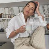 So schön kann es also aussehen, wenn das eigene Outfit zum Interieur der Wohnungpasst. Anna Schürrle posiert mit einem Allover-Leinen-Look, bestehend aus einem lässigen Oversized-Hemd und einer ebenfalls weit geschnittenen Hose, auf dem Küchentisch. In der rechten Hand hält sie eine Tasse Tee. Anna mag es aber nicht nur in Sachen Styling clean, sondern allem Anschein auch in der eigenen Küche: Im Hintergrund sieht man ordentlich drapierte Glasgefäße vor einer hübschen Marmor-Wand.