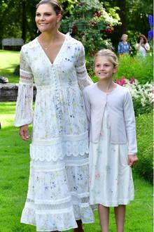 So wählt Estelle von Schweden ebenfallseinweißesSommerkleid, das dank derfloralen Prints zum Hingucker wird. Ein Cardigan in zarten Rosa und weiße Sandalen runden ihren Look ab. Welch ein süßes Style-Match mit Mama Victoria!