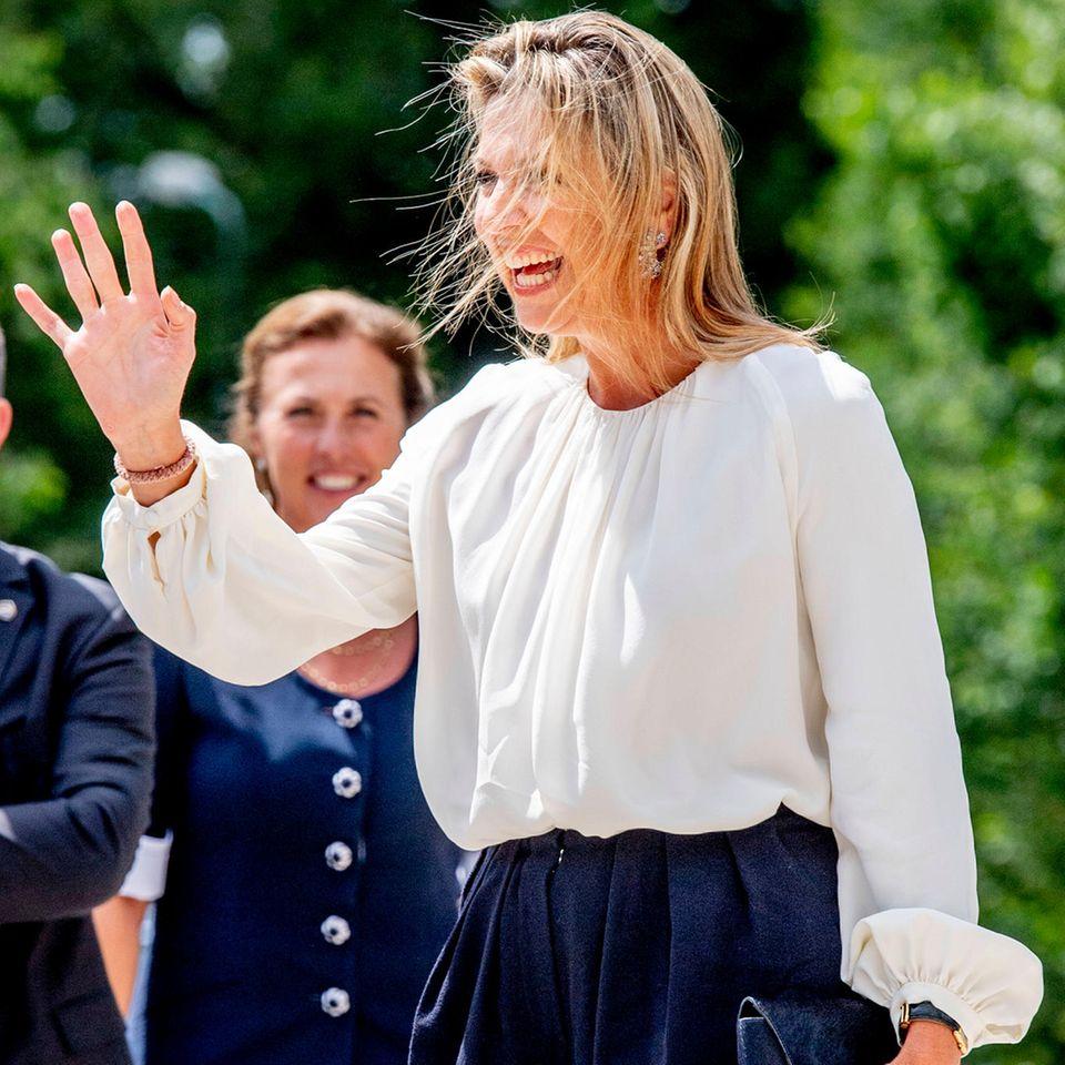 Sonnenschein-Máxima kann einfach nichts aus der Ruhe bringen. Freudig-strahlend winkt sie den Menschen zu - und das, obwohlin dem niederländischen Städtchen Doorn eine steife Brise herrscht. Mitunter ist es sogar so windig, dass Máximas Haare ihr direkt vor die Augen fliegen. Doch ...