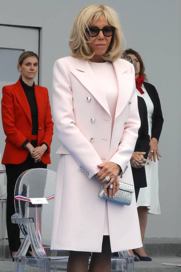 Frankreichs Première dame Brigitte Macron bezaubert am Bastille-Tag 2020 in mädchenhaftem Rosa. Das elegante Ensemble mit silberner Clutch und Two-Tone-Pumps stammt ganz patriotisch vom französischen Luxuslabel Louis Vuitton.