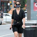 """Mit ihrem schwarzen All-Over-Look beweist Schauspielerin Katie Holmes, dass auch die Gesundheitsschuhe der deutschen Marke Birkenstock echte Fashion-Pieces sind. Die schwarzen """"Arizona""""-Pantoletten mit silberner Hardware kombiniert sie zum Fransenkleid, das durch einen coolen Gürtel aufgepeppt wird. Goldschmuck, eine große Sonnenbrille und ein lässiger Dutt runden das Outfit ab."""
