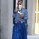 Passt nicht zusammen? Passt doch! Mode-Influencerin Olivia Palermo hat ein Händchen für ungewöhnliche Outfit-Kombinationen. Bei ihrem täglichen Style-Spaziergang durch New York trägt die Unternehmerin diesmal eine grafisch-gemusterte Bluse zum blau-satinierten Maxirock von Max&Co und hochgeschnürte Glitzer-Sneaker.