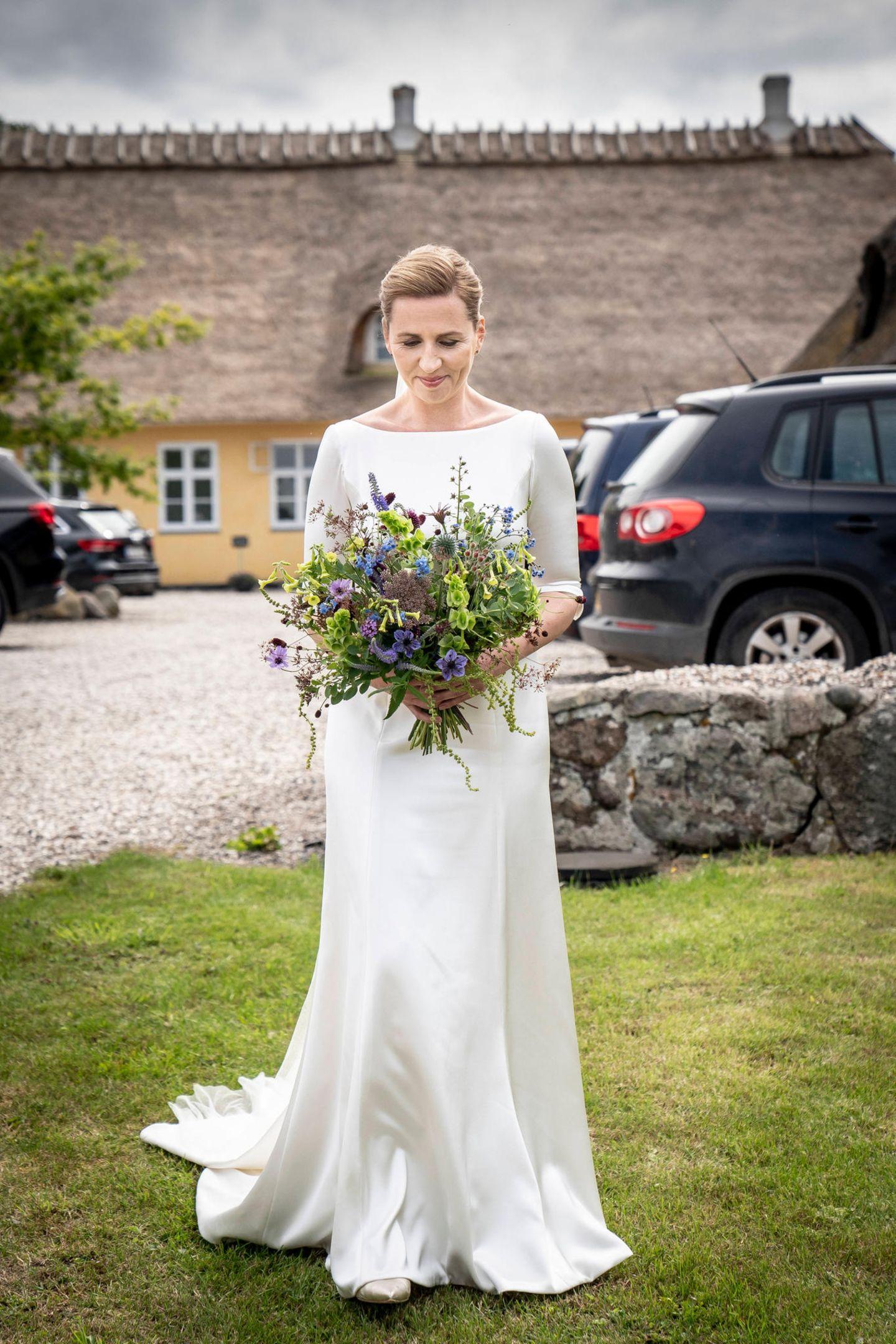 Die 42-Jährige wählt ein schlichtes Kleid: Halblange Ärmel, der U-Boot-Ausschnitt und der leicht ausgestellte Rock erinnern an das Brautkleid von Herzogin Meghan. Das Haar trägt sie hochgesteckt. Besonderer Hingucker ist auch der große Brautstrauß aus Wildblumen.