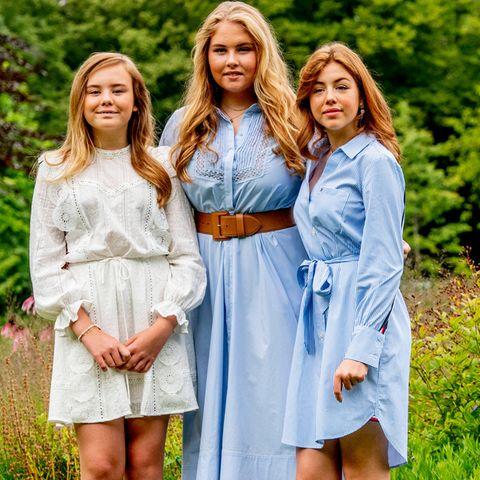 (V.l.) Prinzessin Ariane, Prinzessin Amalia und Prinzessin Alexia sehen beim traditionellen Sommer-Fotoshooting der niederländischen Königsfamilie ganz bezaubernd aus! Für den Fototermin im Garten von Schloss Huis ten Bosch in Den Haag hat sich das Geschwister-Trio spitzenmäßig aufeinander abgestimmt. Ariane trägt ein entzückendes weißes Kleid aus Spitze, ihre ältere Schwester Amalia ein hellblaues mit Spitzeneinsätzen am Dekolleté, inklusive stylischem Ledergürtel. Alexia bleibt zwar dem Farbkonzept treu, hat sich aber für ein - ebenfalls sehr süßes - Hemdblusenkleid mit Taillengürtel entschieden.