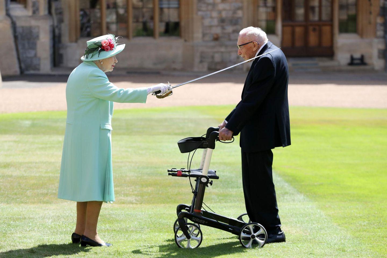 """Mit einem Schwert, daseinst ihrem Vater König George VI. gehörte, schlägt die Queen Tom Moore für seine Verdienste zum Ritter. """"Vielen Dank, eine erstaunliche Menge Geld, die Sie gesammelt haben"""", huldigt sie laut """"Mail Online"""" dem 100-Jährigen. Der soll gescherzt haben: """"Wenn ich jetzt umfalle, schaffe ich es nie mehr hoch."""" Die 94-jährige Queen und der 100-jährige Kriegsveteran - ein rührendes Foto, das man als Royal-Fan einfach gesehen haben muss."""