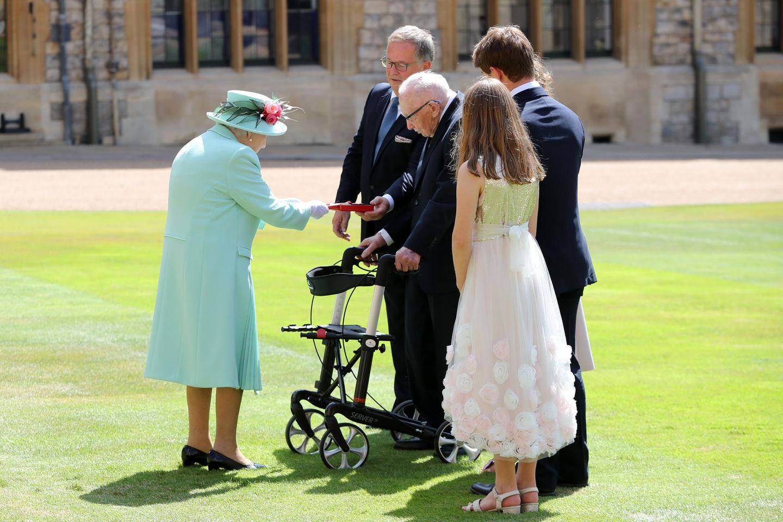 Captain Tom Moor wird von seiner Enkelin Georgia, seiner Tochter Hannah und seinem Enkelsohn Benji begleitet. Hier überreicht ihm die Queen das Abzeichendes Knights Bachelor. Der 100-Jährigedarf sichfortanCaptain Sir Tom Moorenennen.