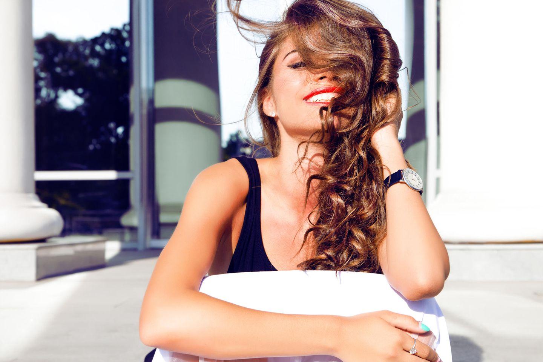 Locken, junge glückliche Frau mit Locken, dunkle Haare