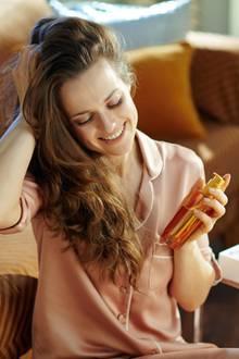 Frau mit Öl, Haarpflege, Frau mit Locken, schöne Haare, Arganöl
