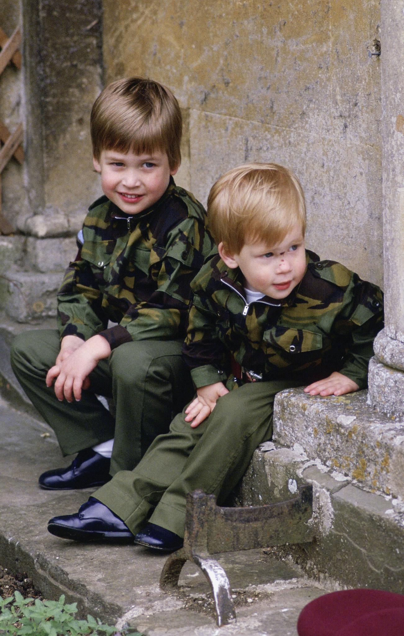 Prinz William (l.) und Prinz Harry (r.) sitzen in einer Armeeuniform zusammen auf den Stufen des Highgrove House am 18. Juli 1986 in Tetbury, England.