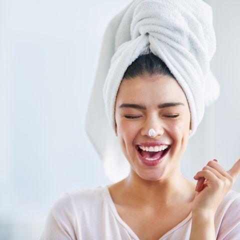 Glückliche Frau trägt Pflege auf das Gesicht auf