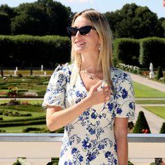 Bei einer Rosentaufe im Hannoveraner Schloss Herrenhausen sieht man Ekaterina von Hannover seit Langem wieder in der Öffentlichkeit. Die Frau von Ernst August Erbprinz von Hannover zeigt sich stilvoll in einem sommerlichen Look. So wählt sie ein weißes Dress mit einem edlen Blumenmuster in royalem Blau. Besonderer Hingucker: die elegante Knopfleiste an der Vorderseite ihres Kleids. Dazu kombiniert Ekaterina von Hannover eine schwarze XL-Sonnenbrille im Cat-Eye-Stil sowie eine schwarze Fransen-Handtasche.