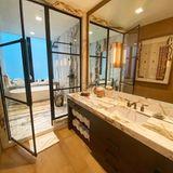 Ein Bad in einem Bad – so ähnlich könnte man Gigi Hadids Badezimmer beschreiben. Es besteht aus einer luxuriösen Nasszelle aus Marmorsamt Badewanne und Dusche. Getrennt durch eine schicke Glastür befindet sich ein großer Waschtisch mit dunklen Unterschränken sowie einem XL-Spiegel davor. Weiße Handtücher runden das Interior der Wellness-Oase ab.