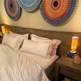 Auf Erdtöne und Naturmaterialien setzt Gigi Hadid in ihrem Schlafzimmer. Das große Doppelbett ist umrahmt von dunklem Holz – passend dazu werden auch die Nachttische gefertigt. Für eine Wohlfühlatmosphäre sorgen die beiden Nachttischlampen. Kreiert aus buntem Porzellan dauerte ihreHerstellung Jahre, wie DesignerSean Forest Roberts auf Instagram verrät. Denn: Der Künstler hatte nie zuvor Lampen aus Porzellan entwickelt. Es sei Gigis Vision gewesen, die ihn dazu bewegten, sich an das Projekt heranzuwagen, so der Designer.