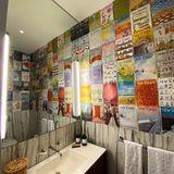 """Das kleine Bad ist mit zahlreichen Magazin-Covern des New Yorker """"gefliest"""" und wird zu Marmor sowie zu einem XL-Spiegel kombiniert. Leuchtstoffröhren sorgen für helles Licht, ein Körbchen aus Bast für wohlige Wärme."""