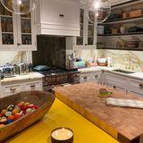 Die Küche richtet Gigi Hadid im modernen Landhaus-Stil ein, setzt auf weiße Fronten, eine Arbeitsplatte aus Marmor sowie auf goldene Armaturen. Dank einer großen Bambusplatte auf der Kücheninsel hat die Hobby-Köchin viel Platz zum Schneiden der Zutaten und Vorbereiten von Gerichten. Besonderer Hingucker: eine Holzschale mit vielen alten Billardkugeln darin.