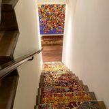 Ein bunter Teppich ebnet Gigi Hadid den Weg herunter. Am Ende der Holztreppe wartet erneut ein Kunstwerk von Austyn Weiner.