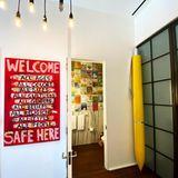 Eine stylishe Lampenkonstruktion, ein gelber XXL-Kugelschreiber und ein Kunstwerk vonEamon Harrington begegnen einem auf dem Weg in ein kleines Badezimmer.