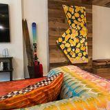 Gegenüber der Couch-Landschaft sticht vor allem ein Kunstwerk aus dunklem Blau und Gelbtönen ins Auge: eine Kreation der US-amerikanischen Künstlerin Austyn Weiner. Platziert auf dunklem Holz kommt es besonders gut zur Geltung.