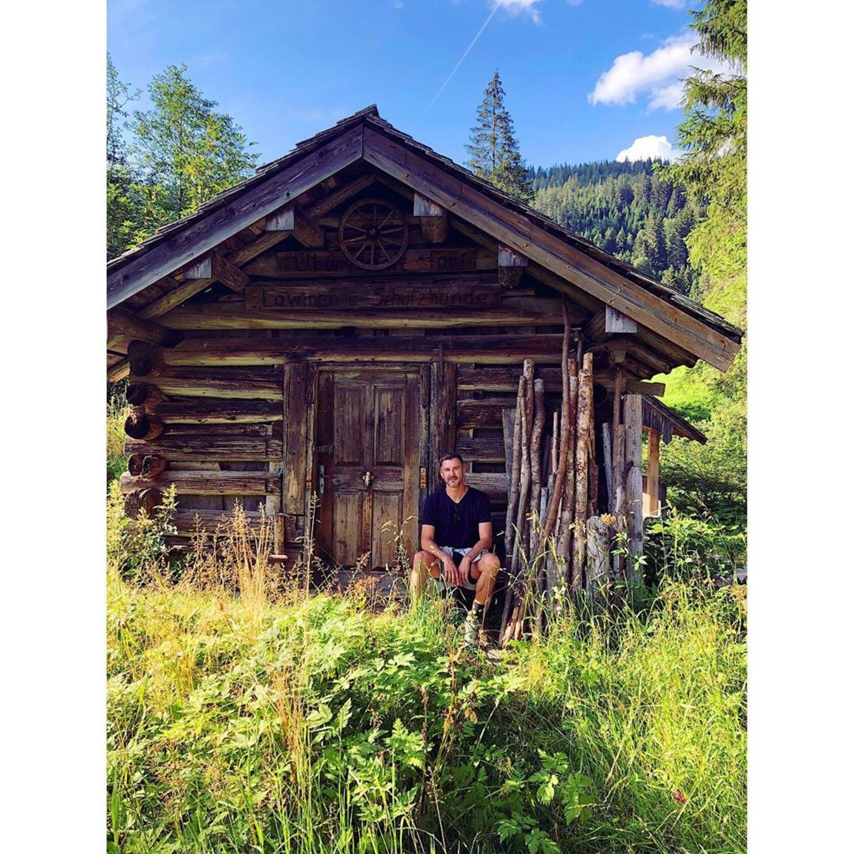 Ein Männlein sitzt vor derHolzhütte und genießt die schöne Natur um sich herum. Es ist Jochen Schropp, der seinen Fans einen Urlaubsgruß via Instagram sendet und sich aus dem Kleinwalsertal in Österreich meldet.