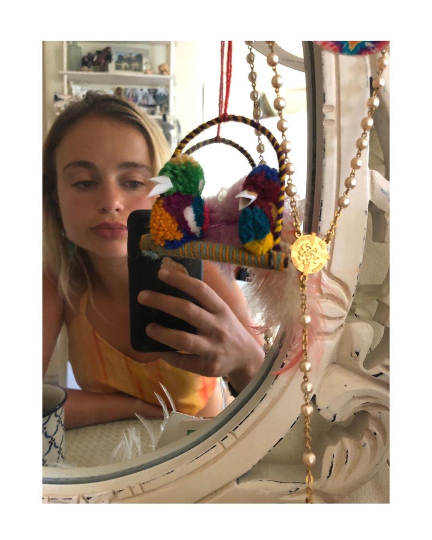 Der Boho-Touch zieht sich durchs ganze Haus bis ins Schlafzimmer: Der Spiegel ist im Shabby-Chic, daran baumelt Schmuck. Im Hintergrund ist ein weißes Regal mit vielen Bildern zu sehen.