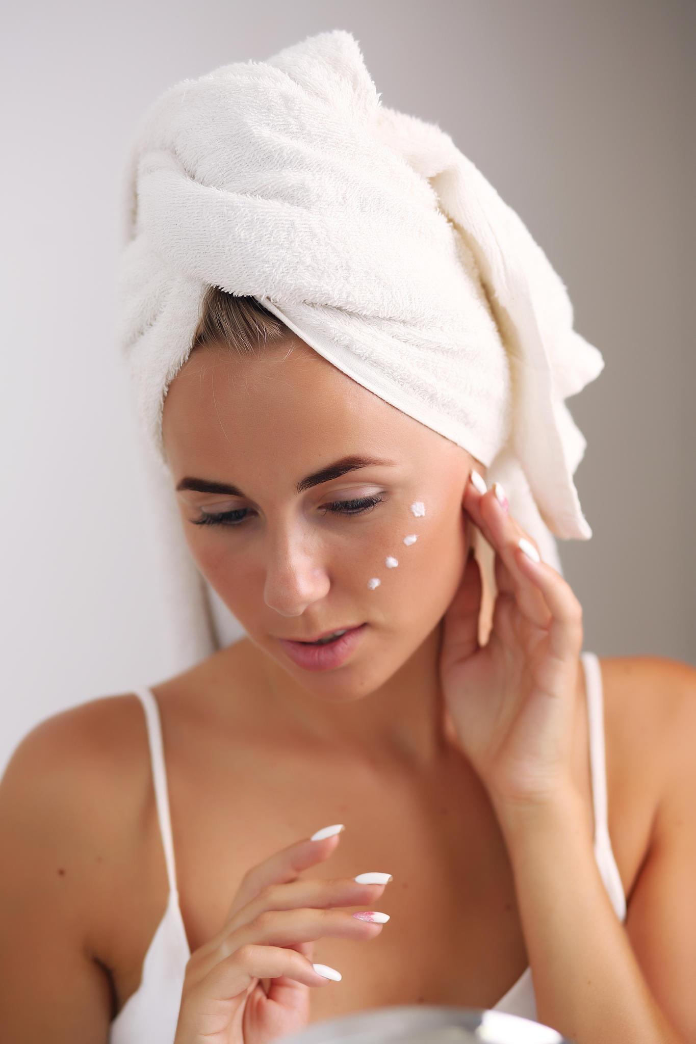 Frau cremt ihr Gesicht ein, Tagespflege für die Haut