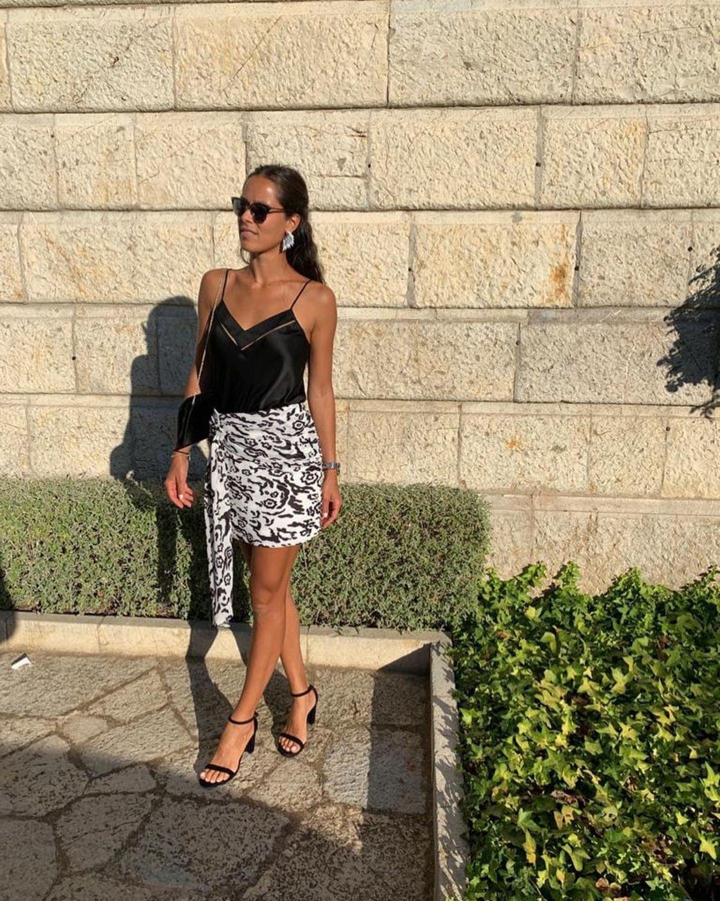 Ana Ivanovic zeigt, wie elegantes Sommer-Styling geht: Schlichtes Top, gemusterter Rock, dazu auffällige Ohrringe und schwarze Schuhe, Tasche und Sonnenbrille - volle Punktzahl für diesen luftigen Look.