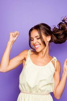 Optimistische Frau hebt Fäuste und tanzt vor violettem Hintergrund