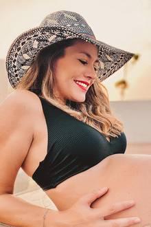 """In der 35. Schwangerschaftswoche entsteht dieses Foto von Fiona Erdmann. Darauf zu sehen ist das Model, das sich eine Abkühlung imPool gönnt und ihreXL-Babykugelim Bikini präsentiert. Liebevoll hält sie ihre wachsende Körpermitte in den Händen. """"Krass, wie riesengroß mein Bauch aussieht!"""", kommentiert Fiona ihr Erinnerungsfoto auf Instagram."""