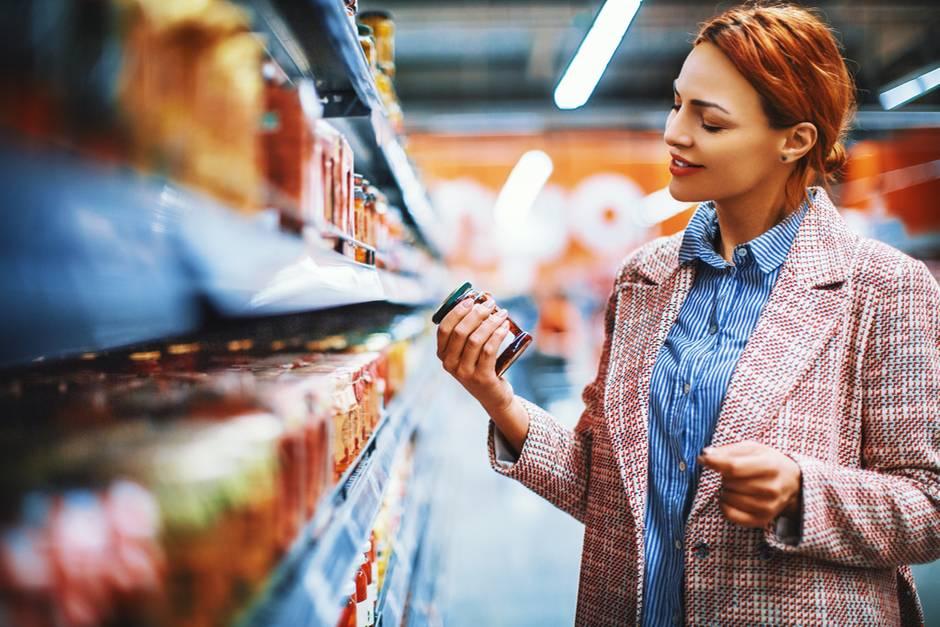 Frau betrachtet Glas im Supermarkt