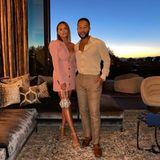 Für ein romantisches Date haben sich Chrissy Teigen und John Legend schick gemacht: Das Model trägt ein rosafarbenes Kleid mit tiefem V-Ausschnitt, kleinen Knöpfen und Puffärmeln, der Oscar-Preisträger setzt auf ein gepunktetes Hemd und eine helle Hose.