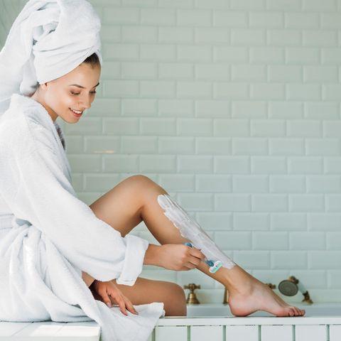 Lächelnde Frau rasiert sich die Beine im Badezimmer