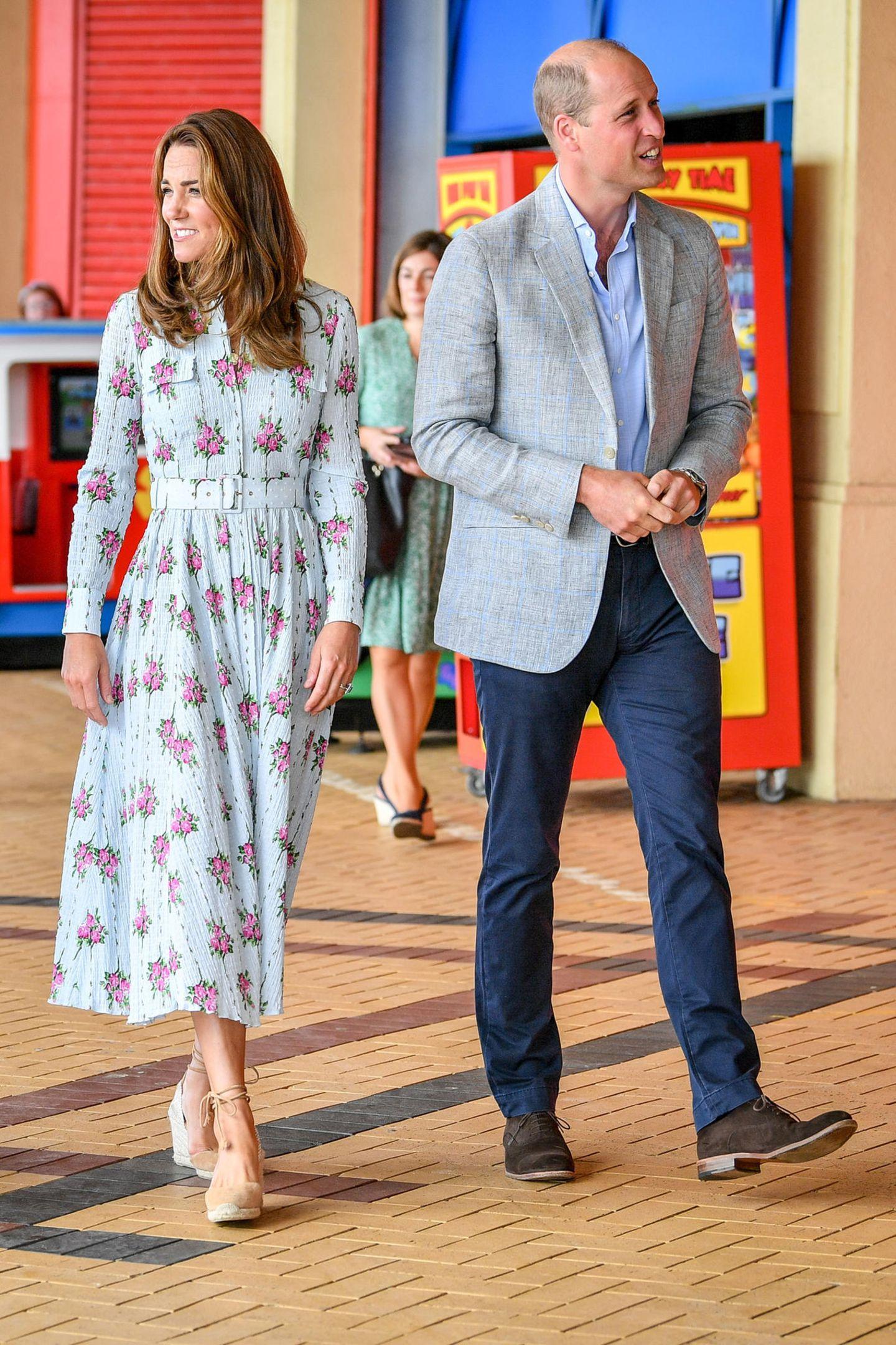 """Kate und William besuchen eine Spielhalle im Süden von Wales. Zu diesem Anlass trägt die Herzogin das """"Aurora""""-Kleid von Emilia Wickstead. Das luftige Material, der florale Print und der elegante Schnitt sind perfekt für einen sommerlichen Termin wie diesen. Dazu kombiniert sie hellbraune Wedges von Castañer."""