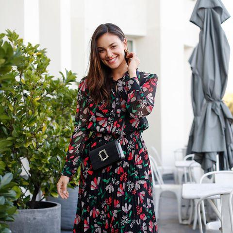 Auf dem Weg zur digitalen Fashion Show von Marc Cain bezaubert Janina Uhse in einem floralen Midi-Kleid. Dazu stylt sie eine schwarze Tasche und schwarze Stiefeletten - ein perfekter Look für jeden Tag.