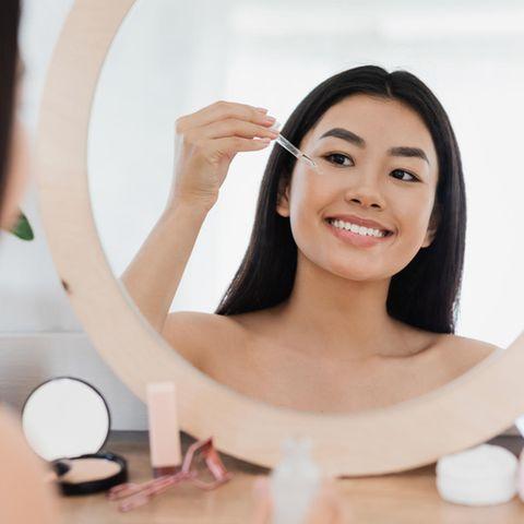 Schöne Frau  trägt Öl vor Kosmetikspiegel auf