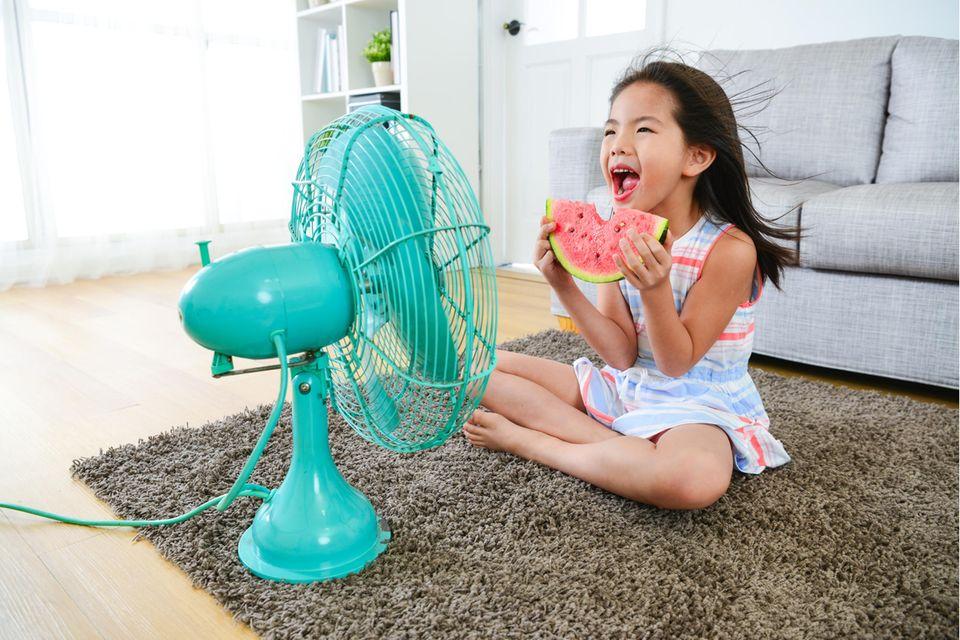 Mädchen sitzt vor einem Ventilator.