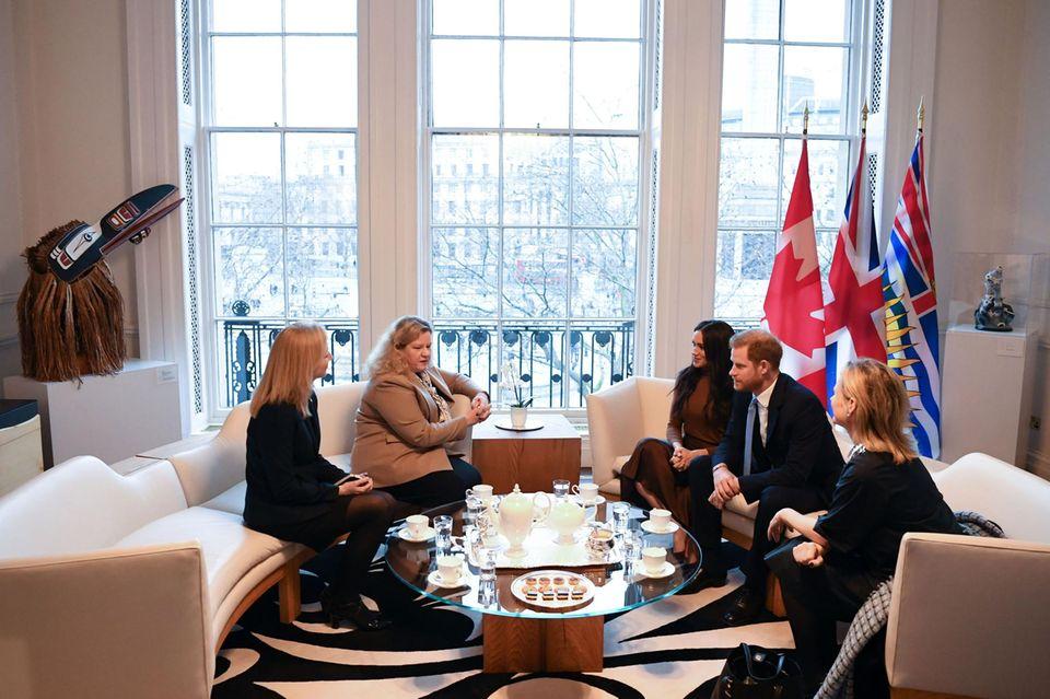"""Herzogin Meghan und Prinz Harry sprechen im Canada House mit Mitarbeitern. Dass nur wenige Stunden später """"The Sun"""" über einen Rückzug des royalen Paars berichten wird, ahnt keiner."""