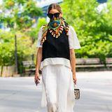 Reduzierte klassische Schwarz-Weiß-Looks lockert Olivia Palermo mit farbenfrohen Design-Schals auf, die sie zum Dreieck gebundenüber Nase und Mund trägt.