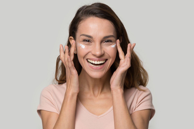 Lachende Frau trägt Creme unter die Augen auf