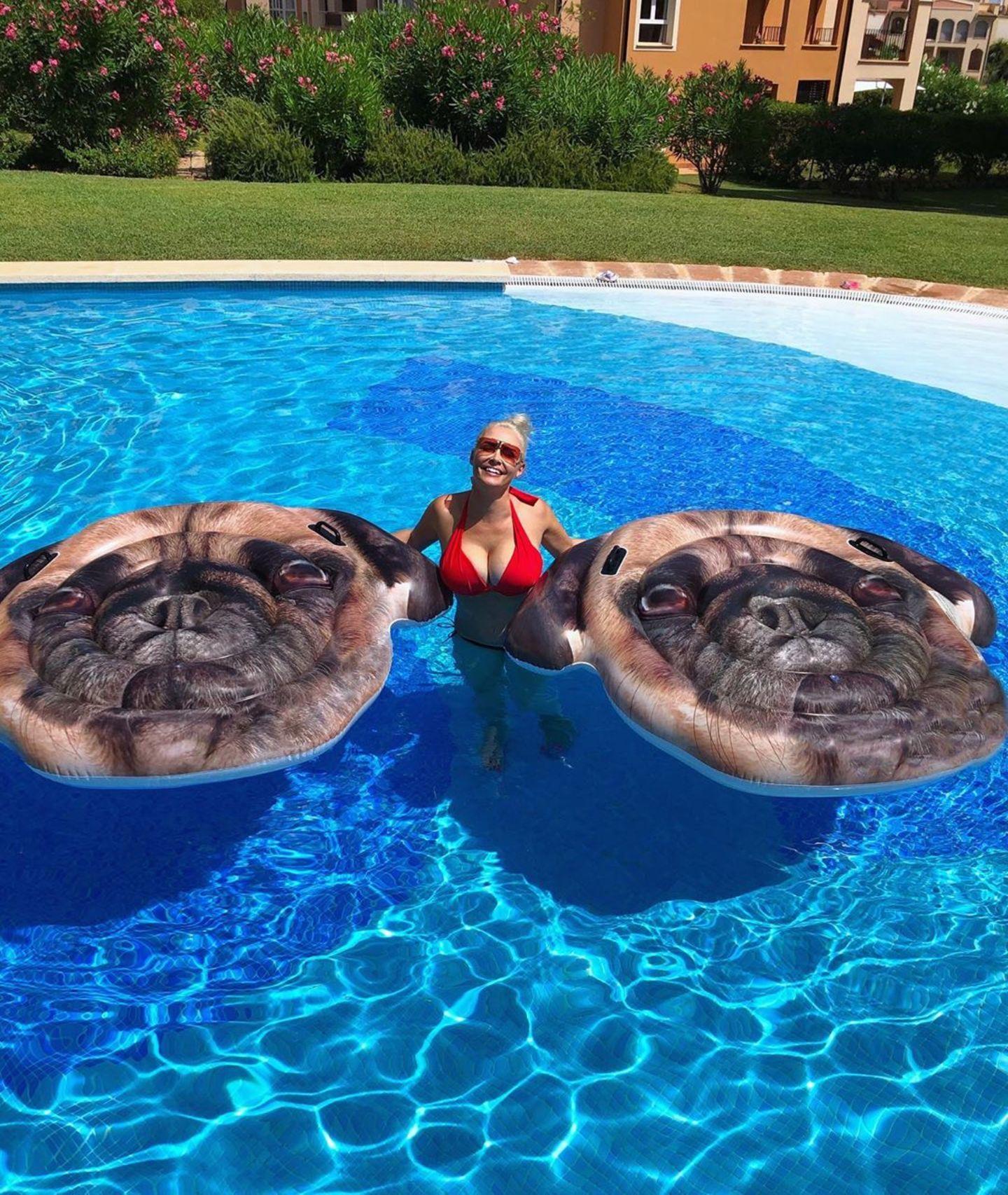 """""""Manchmal braucht man 2 Möpse, die dich über Wasser halten. Früher Lebensmotto, heute sind wirklich nur die Luftmatratzen gemeint"""", schreibt Daniela Katzenberger auf Instagram. Zu sehen ist die Kult-Blondine im knappen Bikini im Pool. An ihrer Seite hat sie zwei Mops-Luftmatratzen, die den witzigen Post erklären."""