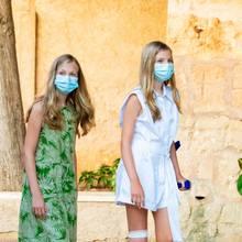 ... Leonor wählt ein grünes Kleid mit tropischem Print von Mango mit passenden Schuhen von Ria Menorca,Sofía trägt einen weißen Jumpsuit von Zara und Schuhe von Avarcas MIbo - die Flats, die beide tragen sind auf der Nachbarinsel Menorca produziert und typisch für die Balearen-Region. Beide setzen somit auf bezahlbare Looks - wie ihre Mama Königin Letizia auch so oft.Sofiá ist übrigens kürzlich gestürzt und musste am Knie mit fünf Stichen genäht werden - daher Verband und Krücke.